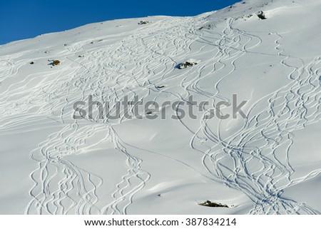 A series of ski tracks through fresh powder snow off piste, down a hill side - stock photo