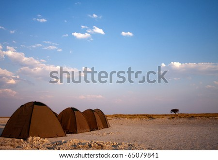 A series of tents on salt pans for wild camping - stock photo