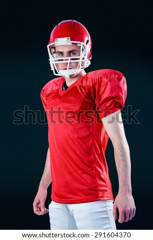 A serious american football player taking his helmet looking at camera with black background - stock photo