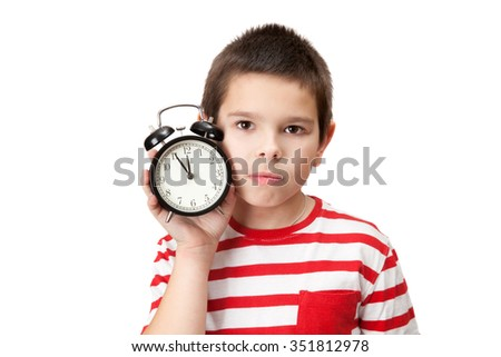 a serious boy with an alarm clock in his hand - stock photo