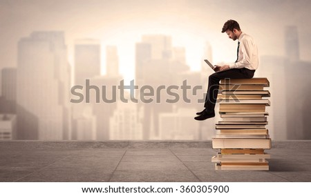 A serious businessman with laptop tablet in elegant suit sitting on a stack of books in front of cityscape - stock photo