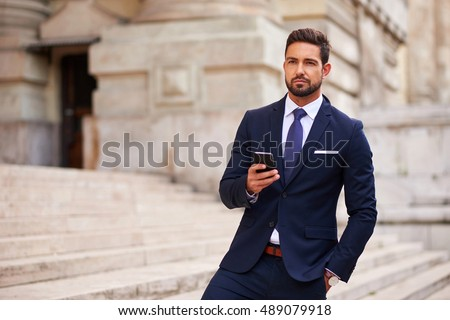 A serious handsome young businessman standing on the stairs while using his phone