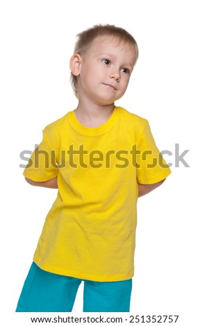 A serious little boy in a yellow shirt on the white background