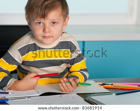 A serious little boy is sitting at the desk - stock photo