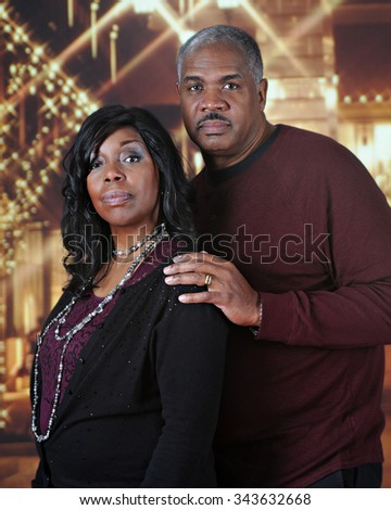 A serious, mature African American couple posing at nighttime outside a Christmas-lit mall.   - stock photo