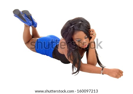 A serious young black woman lying on her stomach on the floor  for white background.