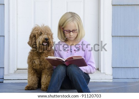 A serious young girl sits on the steps of her house reading a book with her dog next to her - stock photo