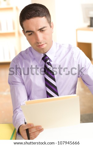 A serious young man looking at a folder in an office setting.