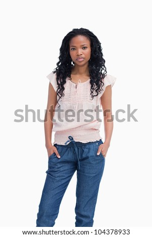 A serious young woman is standing with her hands in her pocket