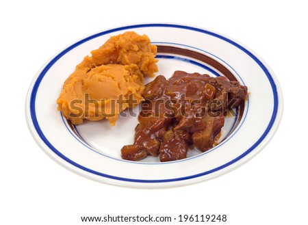 A serving of braised beef in a hot sauce with mashed sweet potatoes on a white background. - stock photo