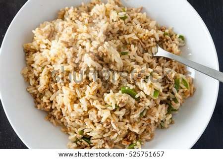 A serving of dirty rice, a traditional cajun and creole dish, in a white bowl with a fork