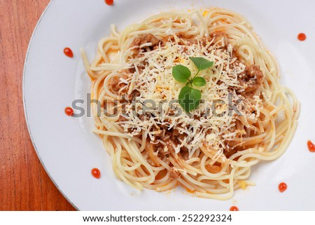 a serving of Italian spaghetti with sauce bolognese and a meat, isolated on wood background - stock photo
