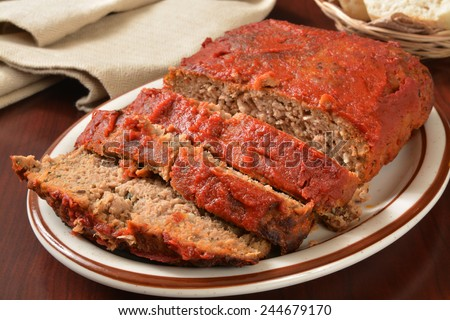 A serving platter with sliced meatloaf covered in tomato sauce - stock photo