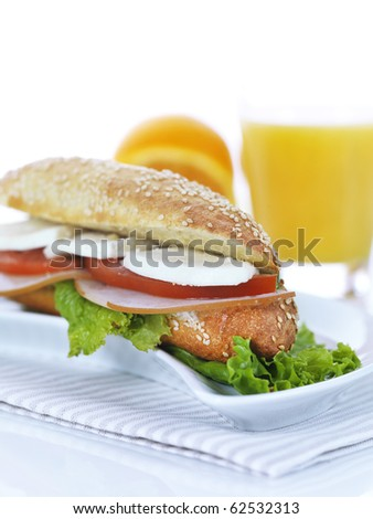 a sesame baguette filled with traditional goat cheese,ham,lettuce,tomatoes and mayonnaise served on a small white dish and a striped napkin and a fresh orange juice.
