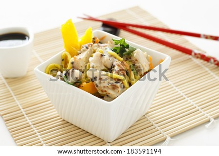 A sesame chicken noodle salad with chopsticks and soy sauce.