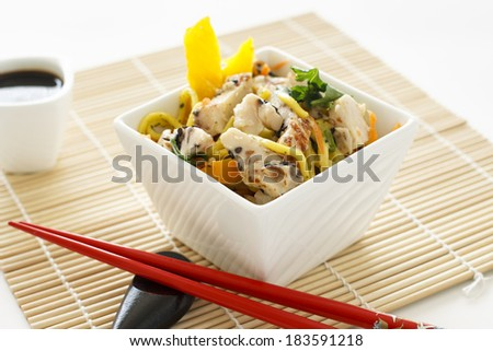 A sesame chicken noodle salad with chopsticks and soy sauce. - stock photo