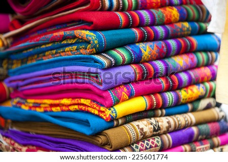 A set of alpaca designed scarves being sold on a cloudy day at the textiles market. - stock photo