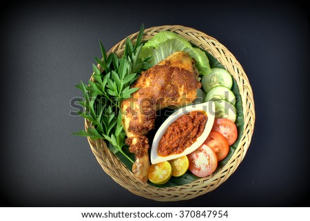 A set of 'Ayam Penyet'. Ayam penyet is Indonesian cuisine. fried chicken dish consisting of fried chicken , served with sambal, slices of cucumbers, tomato, lime. - stock photo