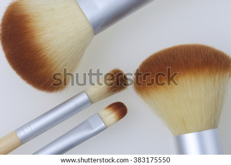 A set of bamboo brushes for applying makeup. Brushes for makeup: blush, eye shadow and correction. Of different sizes and diameters. Yellow and silver color on a white background.