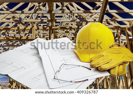 A set of blueprints with hardhat, work gloves and reading glasses with new home construction in background