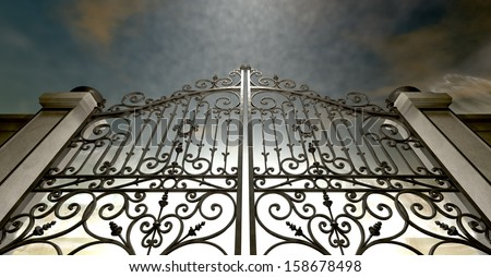 A set of closed ornate gates to heaven under an ethereal light and cloudy afterlife - stock photo