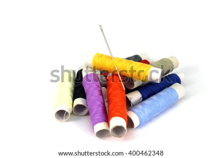A set of colored thread and a needle on a white background - stock photo