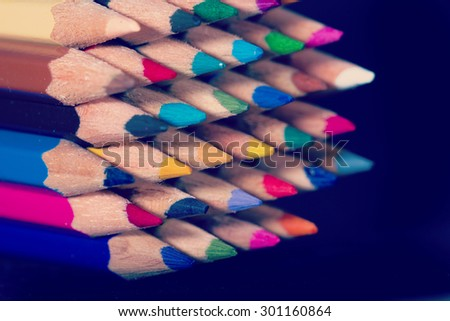A set of colorful pencils on a black background. Image has a vintage effect applied.  - stock photo