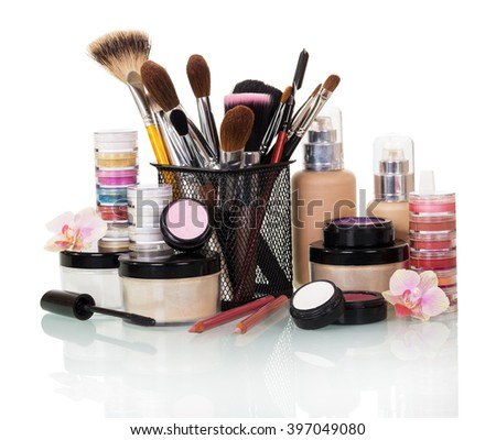 A set of cosmetics and brushes for makeup isolated on white background.