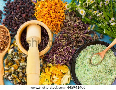 A set of dried flowers and berries, herbs, oak bark, sea salt on old wooden table. Alternative medicine, homeopathy