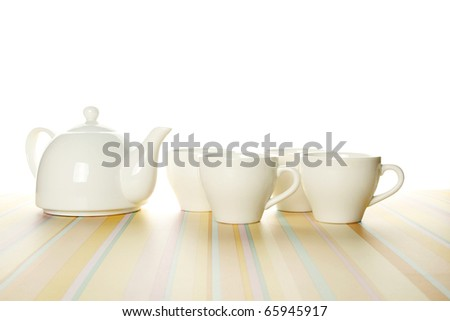 A set of four white cups and a teapot on a light striped background. The upper part of the photo is isolated