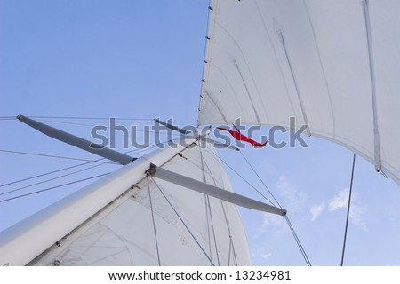 A set of full sails on a sailboat looking up