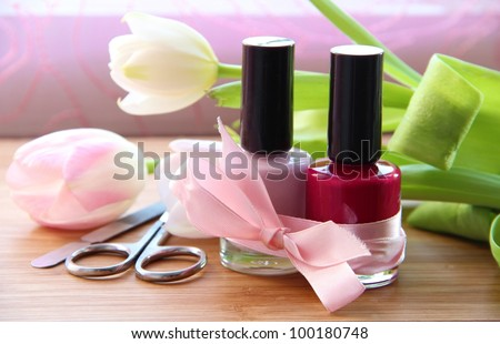 A set of manicure appliances: nail scissors, nail file and two shades of shiny nail polish with pretty tulips on the side - stock photo