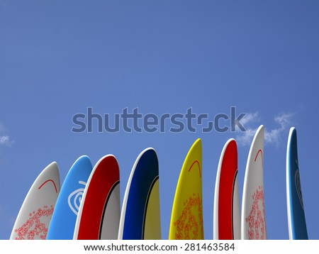 A set of surf boards vertically positioned with a blue sky and some clouds on the background - stock photo