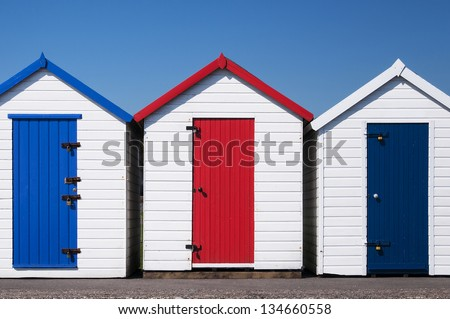 A set of three colorful beach huts at Paignton, Devon, UK on a sunny day. - stock photo