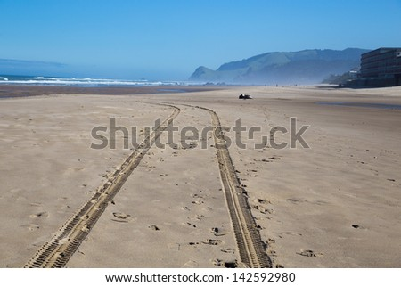 A set of tire mark tracks goes down the beach after a safety vehicle drove through.