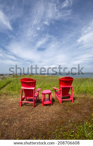 A set of two red chairs and table looking out to the sea with a beautiful big sky above them. - stock photo