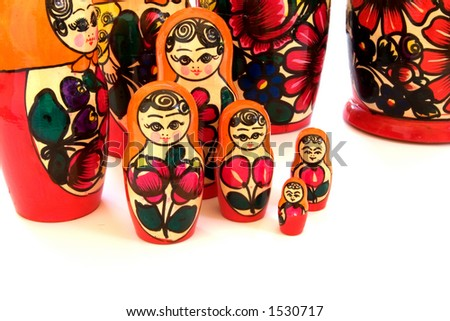 A set of unique Russian Matryoshka nesting dolls with colorful reds and orange decorate a table top. - stock photo
