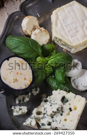 A set of various French and Italian cheeses on the vintage metal plate, served with white wine, herbs and croutons