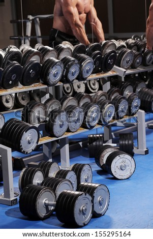 A set up with different dumbbells of different weights and a man in the background  - stock photo
