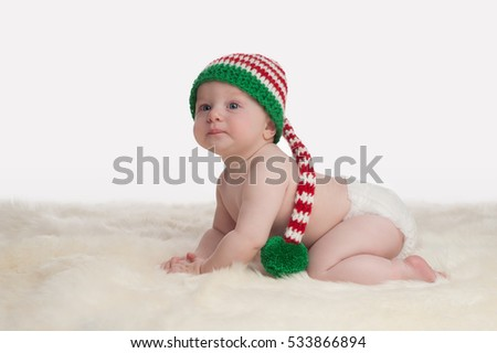 A seven month old baby boy crawling on a sheepskin rug. He is wearing a long, red, white and green striped, Christmas stocking cap. Shot on a white, seamless background.