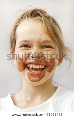 a seven-year-old with chocolate ice cream in the face that looks forward