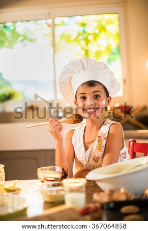 A seven years old girl with chef hat is holding a wooden spoon full of chocolate. She is looking at camera, sitting at a wooden table full of ingredients. She looks delighted. - stock photo