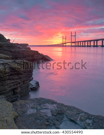 A severn bridge sunrise with fishermen on the left and rocks in the foreground.  - stock photo