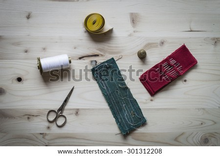 A sewing kit composed of needles on a red pincushion, scissors, measuring tape, spool, thimble, a green sewing test patch and woolen yarn on wooden background. - stock photo