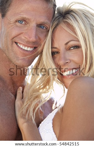 A sexy and attractive man and woman couple smiling and happy in the sunshine at the beach - stock photo
