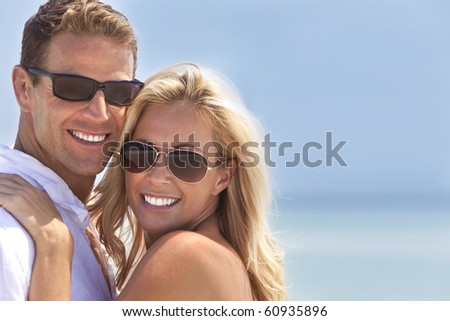 A sexy and attractive man and woman couple smiling and happy wearing sunglasses in sunshine at the beach - stock photo