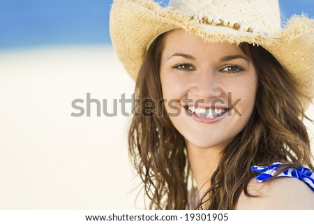 A sexy and beautiful young brunette woman sitting at the beach wearing a straw cowboy hat with golden sand and the sea behind her