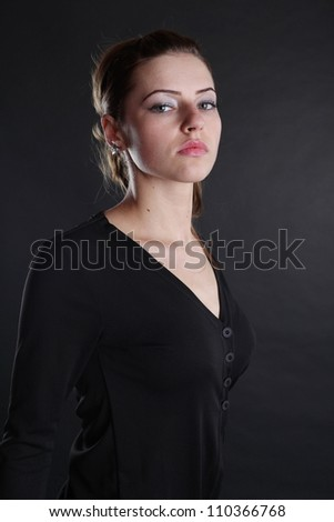 A sexy beautiful girl posing in a studio against a dark background - stock photo