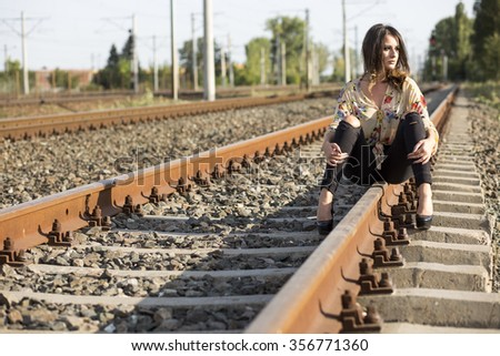 A sexy girl sitting on the old railroad - stock photo