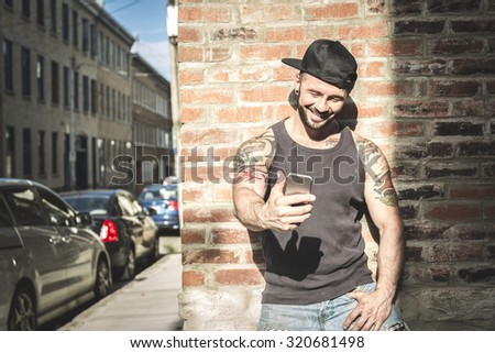A sexy man with tattoo outside in a city street - stock photo
